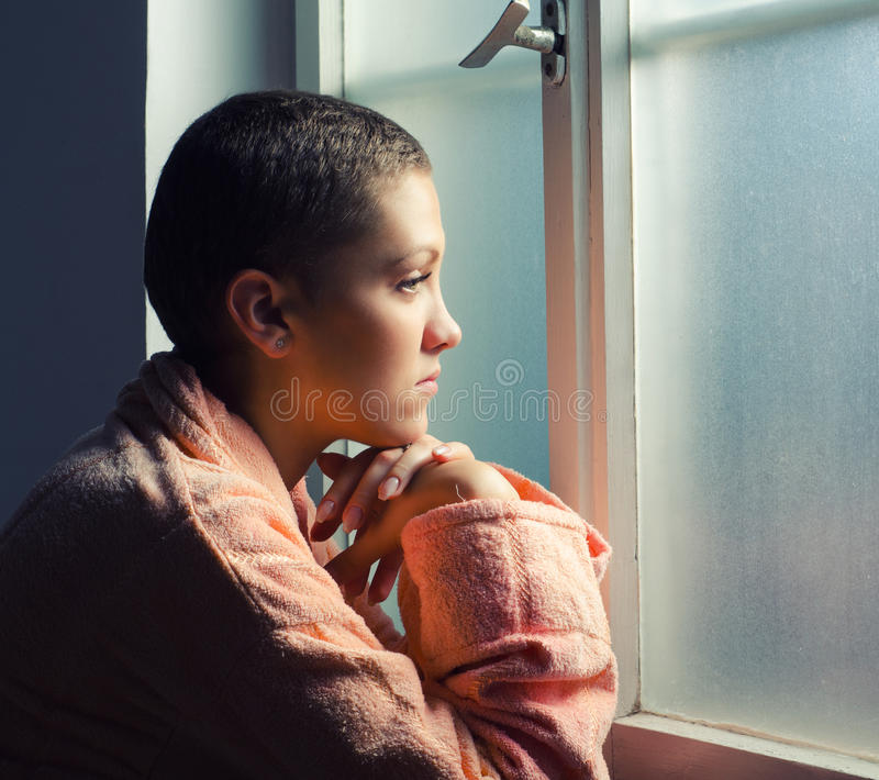 Ung cancerpatient som framme står av sjukhusfönster royaltyfri foto