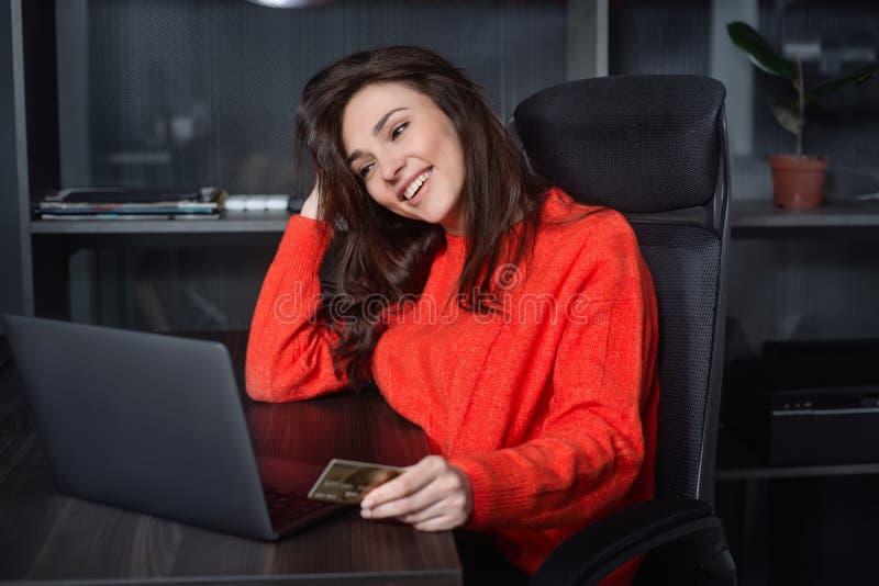 Ung Caucasian affärskvinna som använder kreditkorten för online-betalning royaltyfri foto