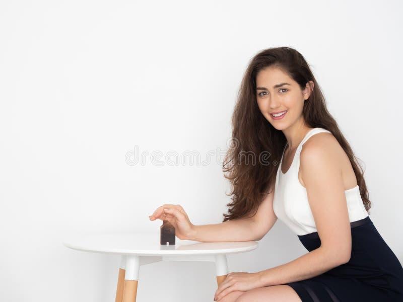 Ung Caucasian affärskvinna som täcker och skyddar ett hus - egenskapsförsäkring och uppehålltäckningsbegrepp royaltyfri bild