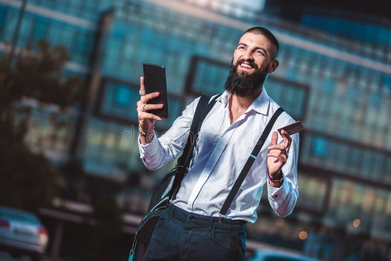 Ung caucasian affärsman som rymmer en utomhus- minnestavla och kreditkort royaltyfria foton