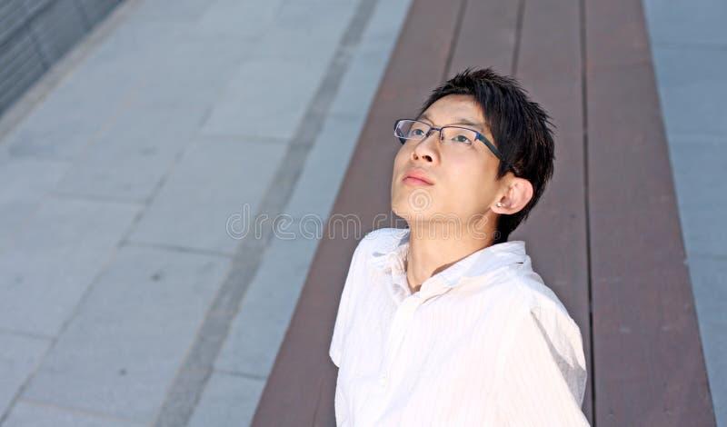 Ung caucasian affärsman som sitter på bänk royaltyfri foto