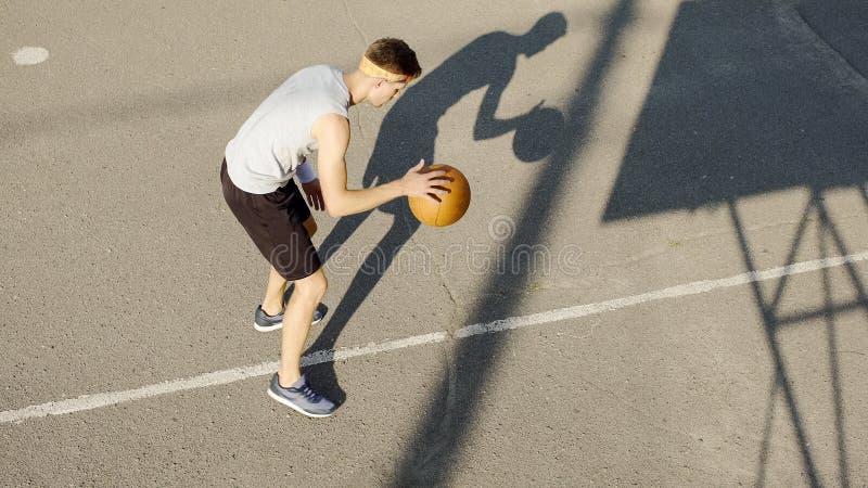 Ung Caucasian basketspelare som dreglar en boll på stadion, sporten och hobbyen royaltyfri fotografi