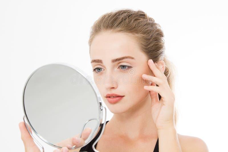 Ung caucasian blond kvinna som ser skrynklor på framsida i spegeln som isoleras på vit bakgrund hudomsorg och makeupbegrepp arkivfoto
