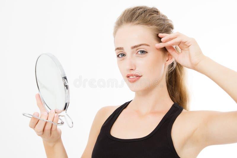 Ung caucasian blond kvinna som ser skrynklor på framsida i spegeln som isoleras på vit bakgrund hudomsorg och makeupbegrepp royaltyfria bilder