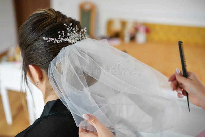 Ung Caucasian brud som får hennes hår förlorad hennes bröllopdag arkivbild