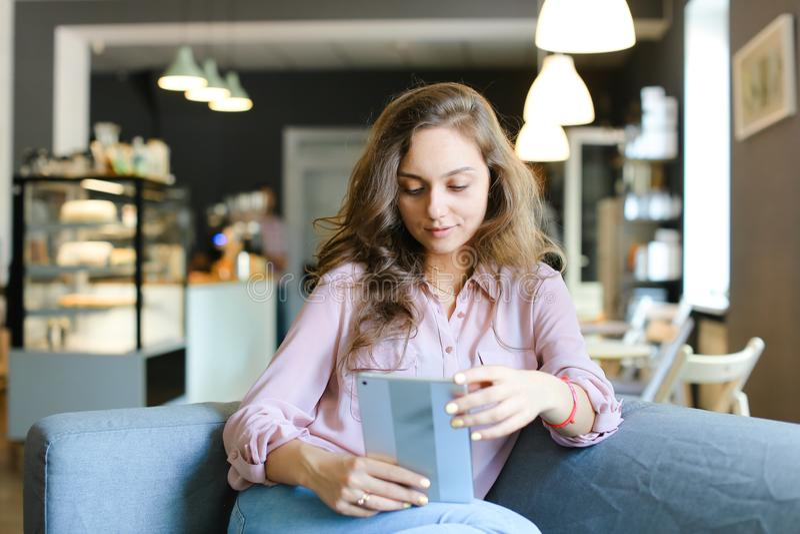 Ung caucasian flicka som sitter på soffan på kafét och använder minnestavlan royaltyfria foton