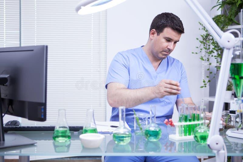Ung caucasian forskareman som tar en prövkopia av lösningen från en provrör royaltyfria foton