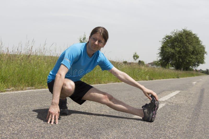Ung caucasian joggersträckning royaltyfri fotografi