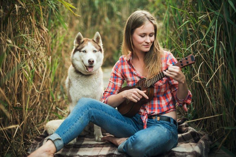 Ung caucasian kvinna med hunden som spelar ukulelet fotografering för bildbyråer