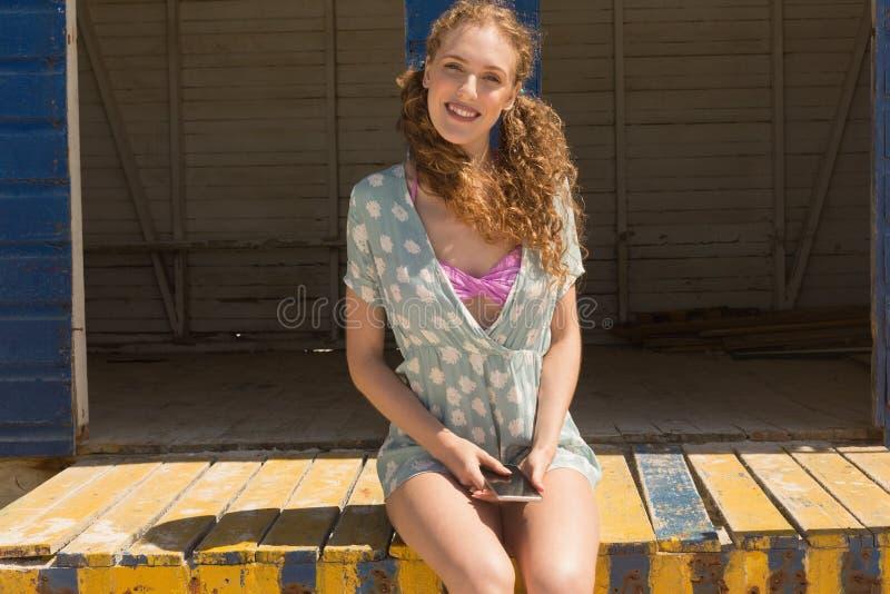Ung Caucasian kvinna med mobiltelefonen som ser kameran på strandkoja royaltyfri fotografi