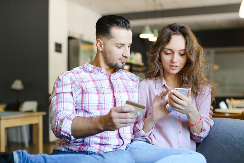 Ung caucasian kvinna och man som använder smartphone- och debiteringkortet på kafét royaltyfri bild