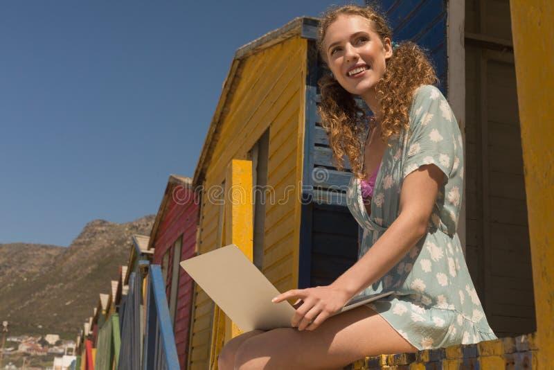 Ung Caucasian kvinna som använder bärbara datorn som bort ser på strandkojan royaltyfria bilder