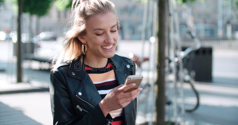 Ung caucasian kvinna som använder telefonen i en stad royaltyfria bilder