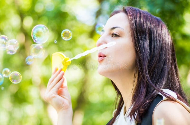 Ung caucasian kvinna som blåser såpbubblor i parkera royaltyfri bild