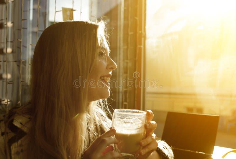 Ung caucasian kvinna som dricker latte i coffee shop fotografering för bildbyråer