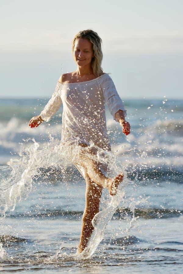 Ung caucasian kvinna som förnyar på stranden royaltyfria bilder