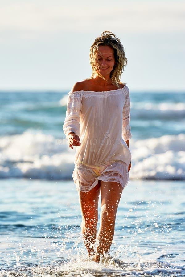Ung caucasian kvinna som förnyar på stranden i sommarafton arkivfoto