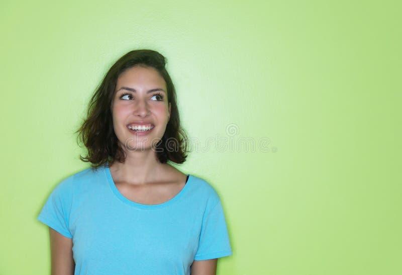 Ung caucasian kvinna som från sidan ser till en grön vägg royaltyfri fotografi