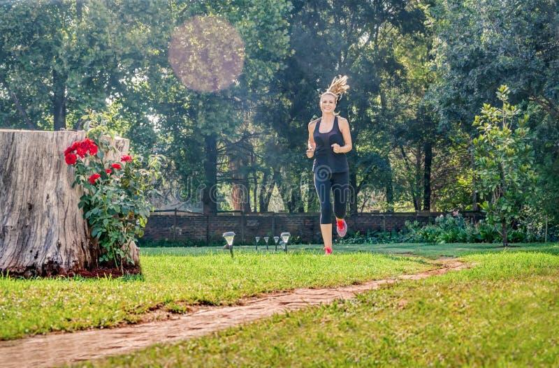 Ung Caucasian kvinna som hemma utbildar i trädgården arkivbild