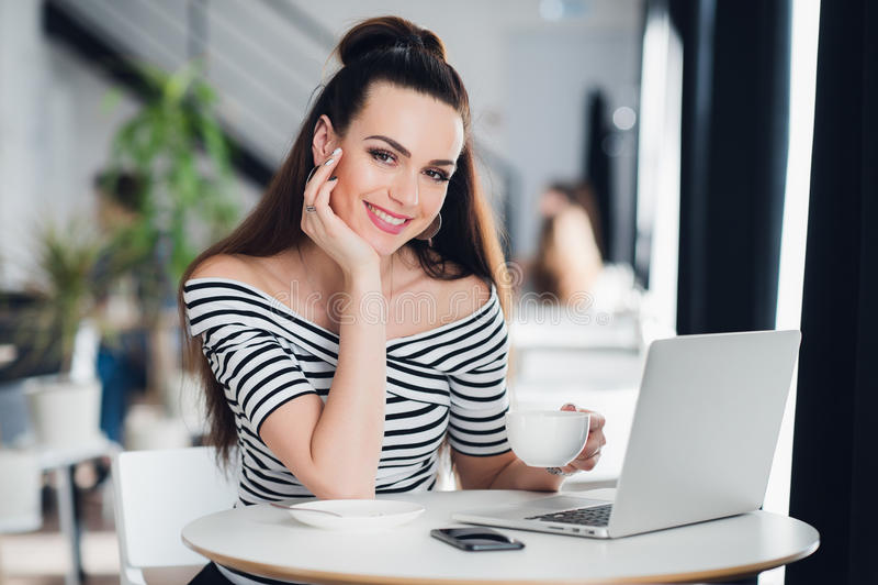 Ung Caucasian kvinna som ler och ser kameran och använder bärbara datorn i kafé royaltyfri fotografi