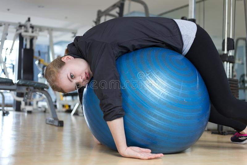 Ung caucasian kvinna som ligger på den blåa gymnastiska bollen som ser evakuerad, tröttat, uttråkat och uttröttat på idrottshalle royaltyfri fotografi