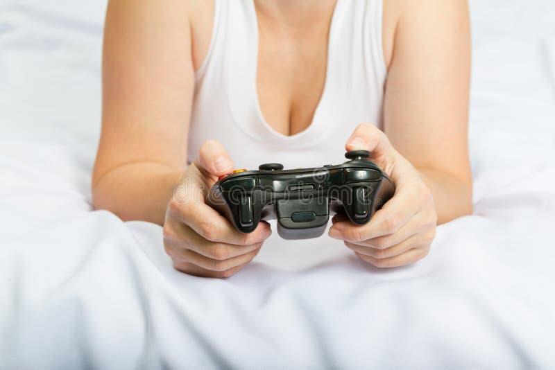 Ung caucasian kvinna som spelar videospelkonsolen på sängen royaltyfri fotografi