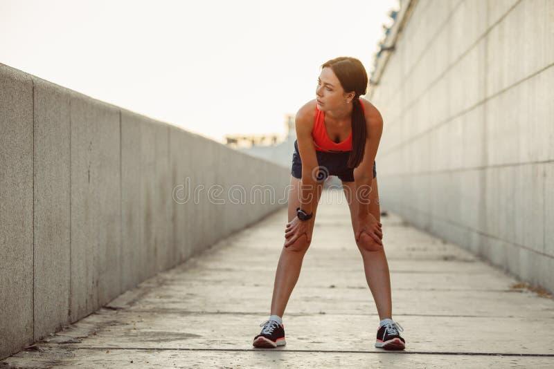 Ung caucasian kvinna som tar andedräkt, når att ha joggat fotografering för bildbyråer