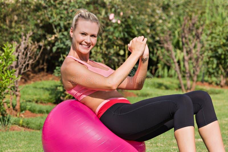 Ung caucasian kvinnautbildning med en rosa idrottshallboll i gården royaltyfria bilder