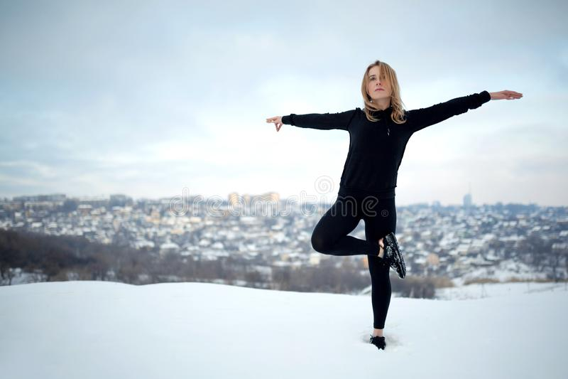 Ung caucasian kvinnlig blondin i damasker som sträcker övning på öppen luft i snöig skogpassform och sportlivsstil royaltyfria foton