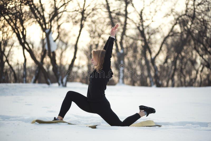 Ung caucasian kvinnlig blondin i damasker som sträcker övning på öppen luft i snöig skogpassform och sportlivsstil arkivbilder