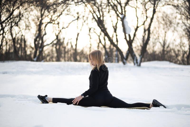 Ung caucasian kvinnlig blondin i damasker som sträcker övningen som sitter på en rad på öppen luft i snöig skogpassform och sport royaltyfri foto