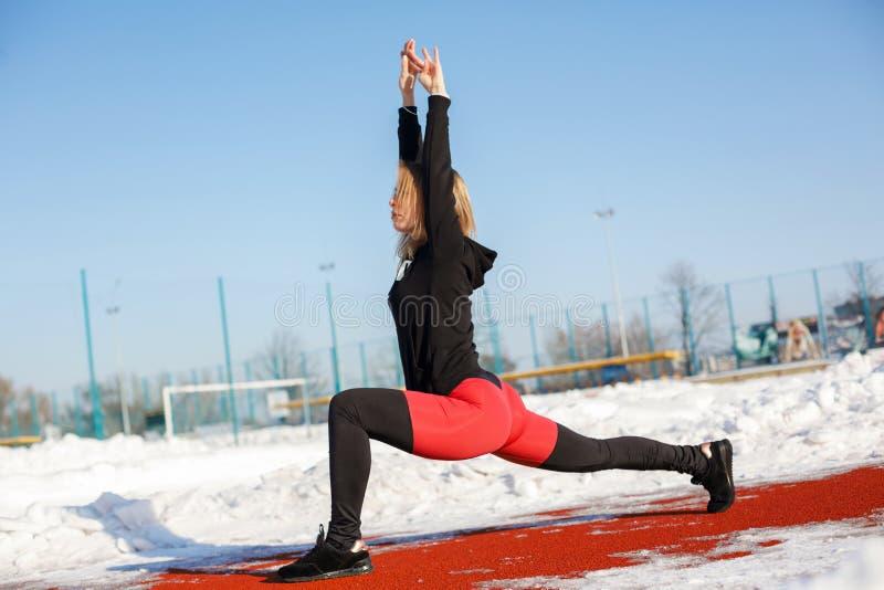 Ung caucasian kvinnlig blondin i röd damasker som sträcker övning på ett rött rinnande spår i en snöig stadion passform och sport royaltyfria foton