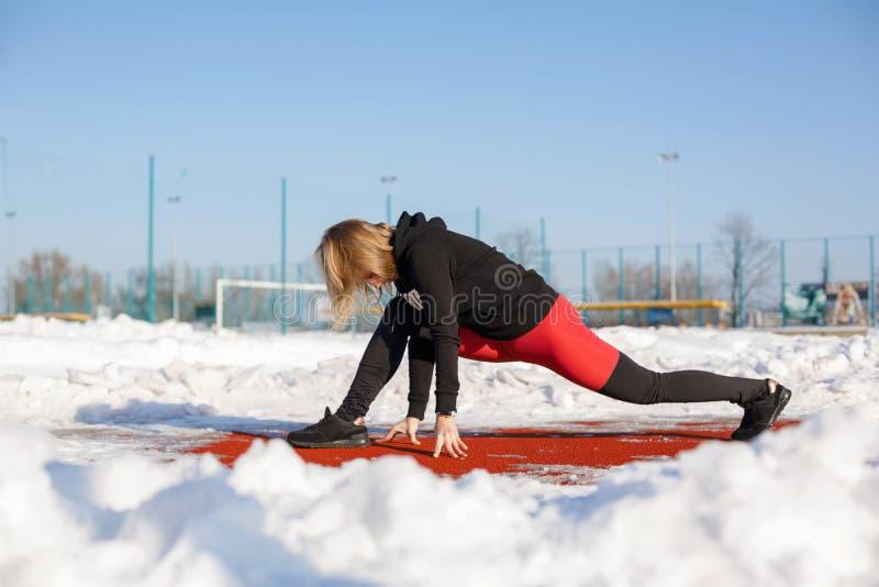 Ung caucasian kvinnlig blondin i röd damasker som sträcker övning på ett rött rinnande spår i en snöig stadion passform och sport royaltyfria bilder