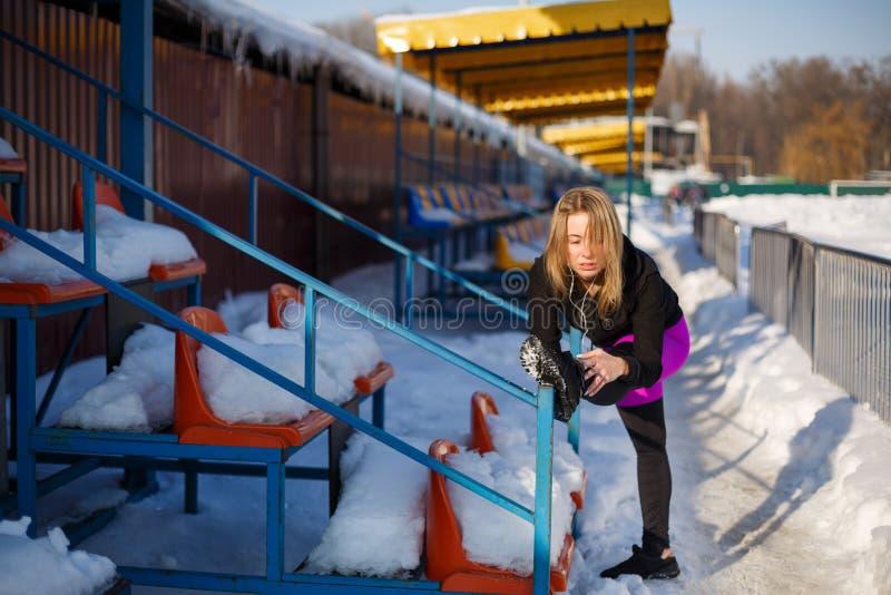 Ung caucasian kvinnlig blondin i violett damasker som sträcker övning på tribun på en snöig stadion passform- och sportlivsstil arkivfoto