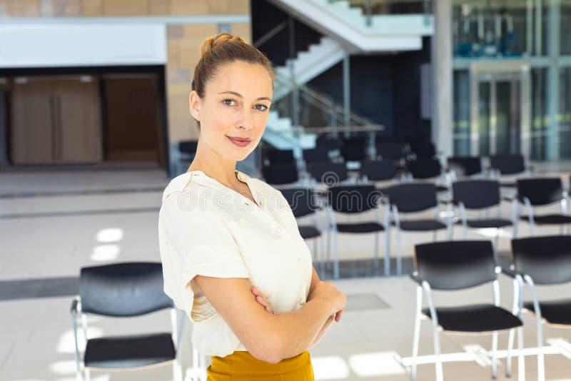 Ung Caucasian kvinnlig ledare som ser kameran, medan stå i tomt konferensrum arkivbild