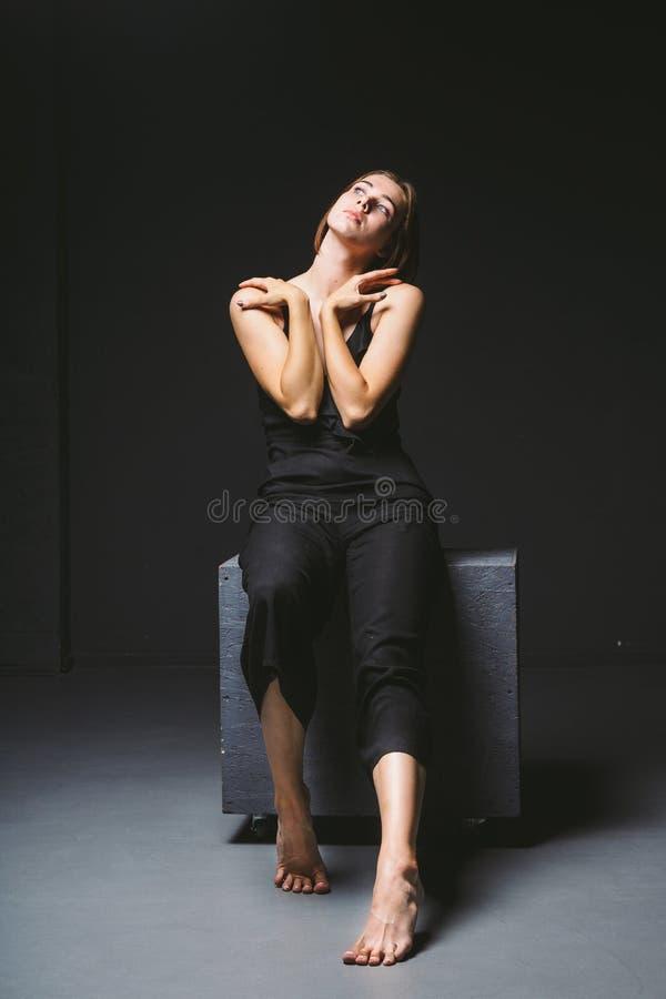 Ung Caucasian kvinnlig modell som poserar i studiosvartbakgrund Flicka som sitter i en svart klänning på en mörk vägg ?mne royaltyfri bild