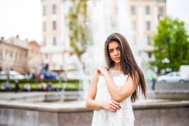 Ung caucasian kvinnlig stående near springbrunn Utomhus- närbildståendekvinna royaltyfria bilder