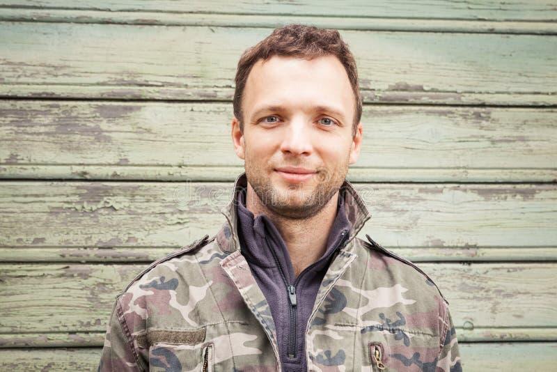 Ung Caucasian man i utomhus- stående för kamouflage arkivfoto