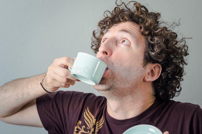 Ung Caucasian man med lockigt hår som dricker en kopp kaffe i hans hand på vit bakgrund arkivfoton