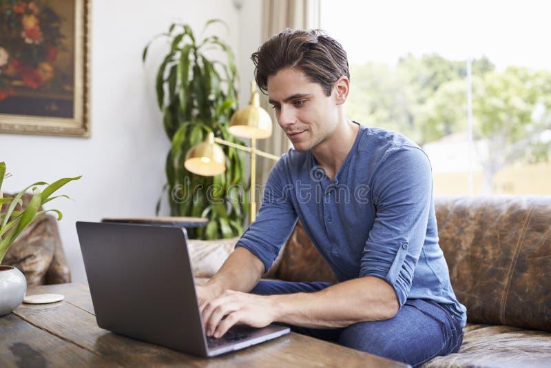 Ung Caucasian man som använder bärbara datorn i en coffee shop arkivfoton