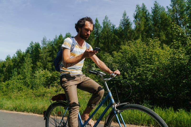 Ung caucasian man som cyklar till och med naturen med smartphonen i hans händer för att navigera arkivbild