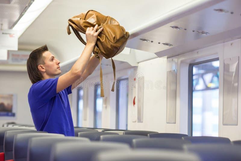 Ung caucasian man som sätter bagage på överkanten arkivfoton