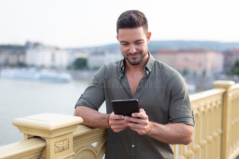 Ung caucasian man som utomhus använder minnestavlan i stad royaltyfria bilder