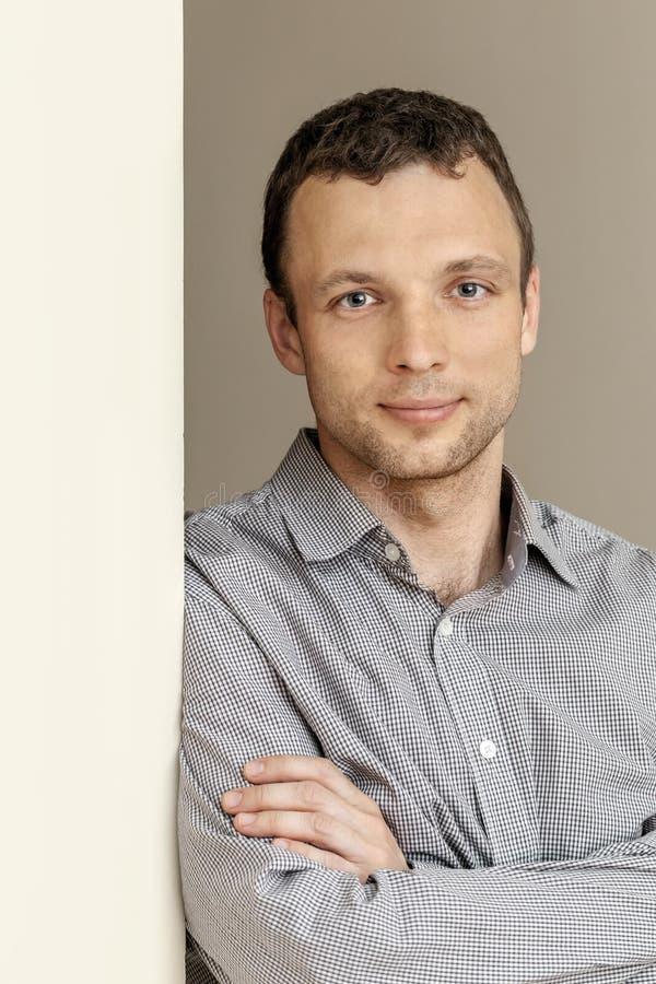 Ung Caucasian man, stående med den gråa väggen arkivfoton