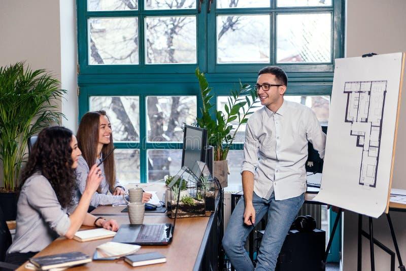 Ung caucasian manlig arkitekt som visar byggnadsplan p? nytt hus till hans kvinnliga coworkers i det stilfulla kontoret royaltyfria foton