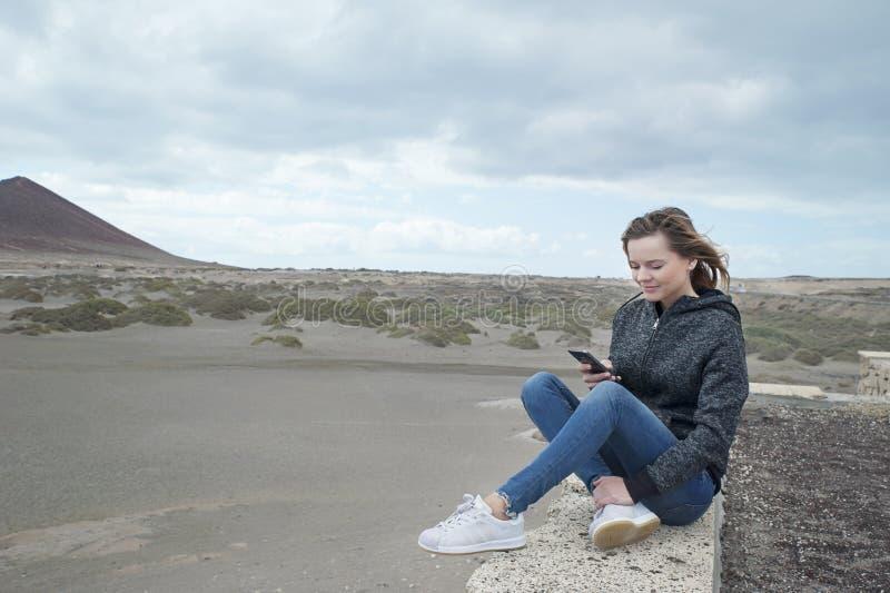 Ung Caucasian millennial kvinna som sitter på en stenbänk av den surfa stranden som är bekant som Playa El Medano, Tenerife, kana arkivfoto