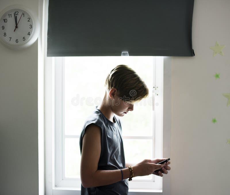 Ung caucasian pojke som använder mobiltelefonen i sovrum fotografering för bildbyråer