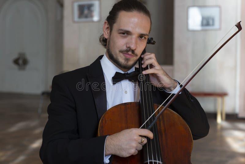 Ung cellist som spelar violoncellen arkivbilder