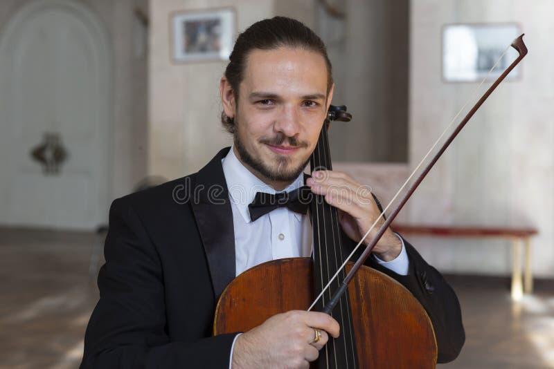 Ung cellist som spelar violoncellen royaltyfri fotografi