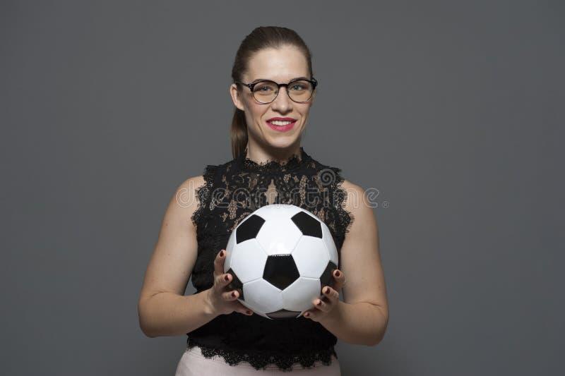 Ung charmig aff?rskvinna - fotbollsfan som rymmer fotbollbollen royaltyfria bilder
